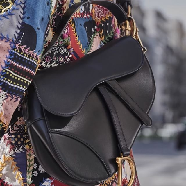 The iconic  Saddle  bag is snapped on the streets of Paris during the shooting of the #DiorAW18 campaign by @FabienBaron. Discover the breadth of variations, all designed by #MariaGraziaChiuri, to find the perfect solution for your everyday needs. Click the link in bio for more. #DiorSaddle