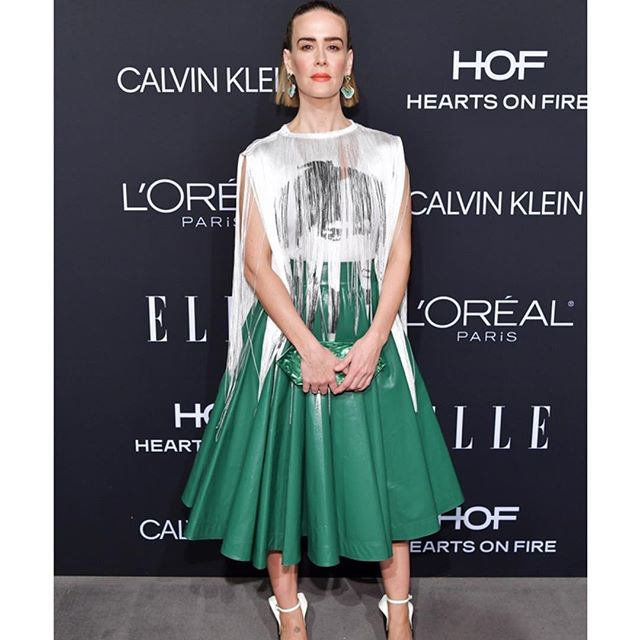 Honoree @mssarahcatharinepaulson makes her entrance at tonight s 25th annual ELLE Women in Hollywood event in a #Spring2019 #CALVINKLEIN #205W39NYC green nylon skirt, white tank top and printed fringe panel featuring #AndyWarhol s #StephenSprouse portrait. Styled with our Kadence suede wing back pumps. @elleusa #ELLEWIH                               Featuring artwork by Andy Warhol  / /  The Andy Warhol Foundation for the Visual Arts, Inc.