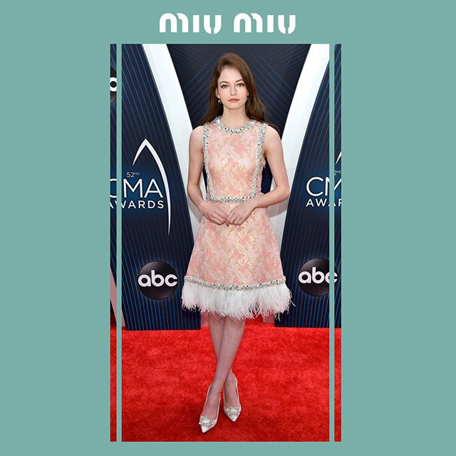 Mackenzie Foy in a Miu Miu jacquard dress embellished with crystals and Marabù feathers while attending the 52nd CMA Awards on November 14th, 2018 in Nashville, Tennessee.  #MiuMiuCelebrities
